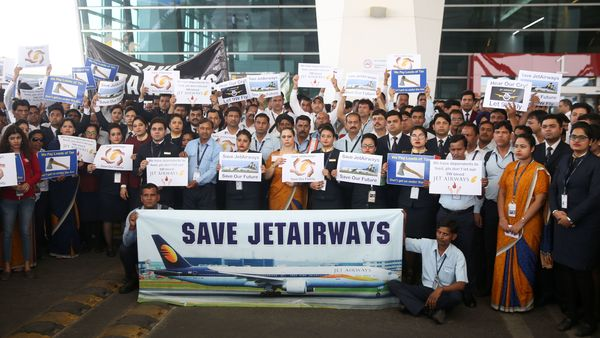 Jet Airways employees hold placards as they gather for a silent march at Terminal 3 of the Indira Gandhi International Airport, in New Delhi on April 13, 2019. - India's Jet Airways extended a suspension of all of its international flights until April 15, the latest blow to the debt-stricken carrier battling to stay afloat. The development on April 12 came after the government said it would investigate Jet's ability to continue flying as lenders seek a buyer to keep the beleaguered airline running. (Photo by STR / AFP)